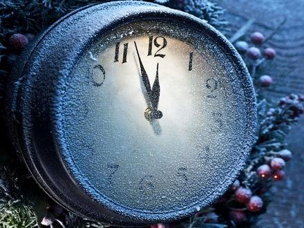 Обои Стрелки часов на циферблате заиндевелого будильника, лежащего в праздничной мишуре, приближаются к цифре 12-времени наступления Нового Года