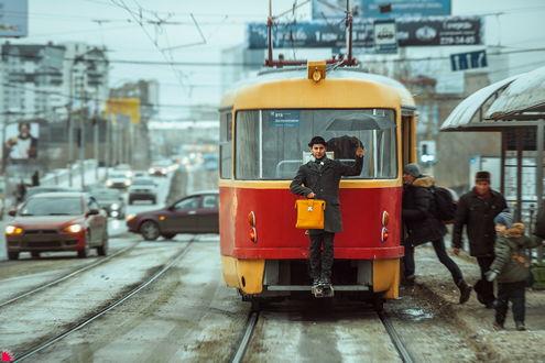 Обои Парень в черной шляпе, держащий в одной руке желтый портфель, в другой черный зонтик, стоящий на площадке снаружи трамвая, остановившегося на остановке, производящего посадку пассажиров, автор Осипов Ежъ Александр