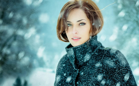Обои Девушка с непокрытой головой стоит под идущим сверху снегом