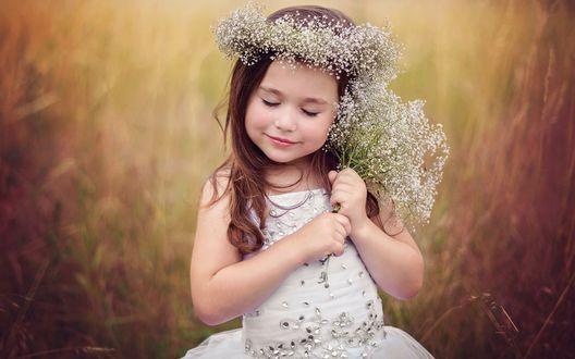 Обои Маленькая девочка закрыв глазки, сидит среди трав в веночке из полевых цветов на голове и держит в ручках букетик из таких же полевых цветов