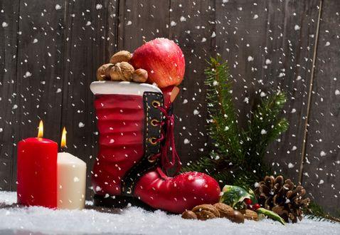 Обои Красный сапог, набитый орехами и яблоками, рядом горящие свечи, орехи и сосновые ветки