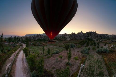 Обои Черный, воздушный шар с виднеющимся пламенем от газовой горелки, парящий в воздухе на рассвете над дорогой, проходящей вдоль ухоженных полей на фоне восходящего солнца на утреннем, безоблачном небосклоне, автор Антон Федорченко