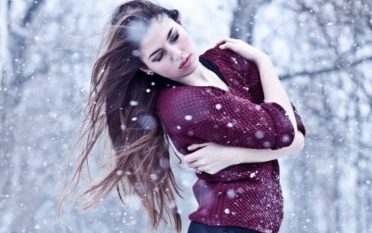 Обои По летнему одетая девушка обняла себя руками, пытаясь согреться под пролетающим снегом