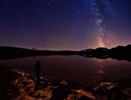Обои Силуэт девушки, стоящей на камнях у берега горного озера на фоне ночного, звездного неба и красивого Млечного пути, автор ambiaso