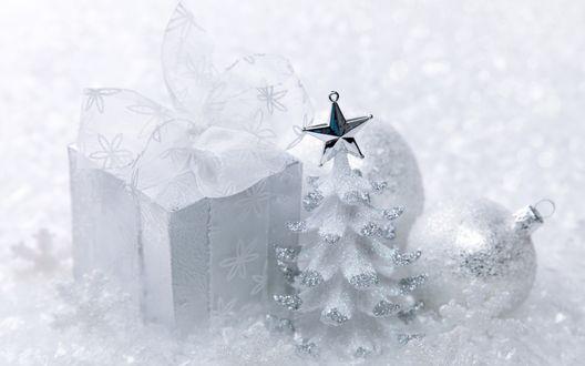 Обои Подарок, новогодние шары и игрушка елка со снежинками лежат на фоне снега