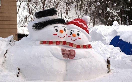 Обои Два снеговика стоят обнявшись друг с другом