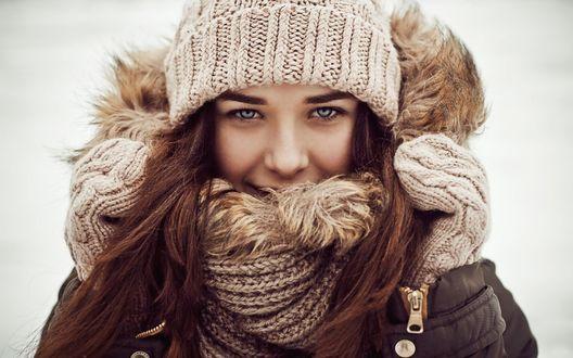 Обои Девушка с синими глазами и в зимней одежде улыбается, подняв руку в варежке к меховому воротнику
