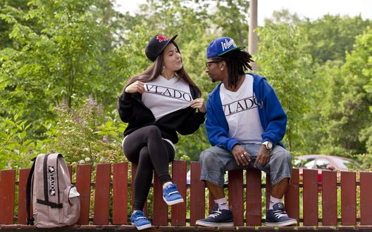 Обои Белая девушка сидя на заборе показывает афроамериканцу надпись на футболке VLADO