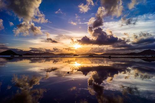 Обои Заходящее за темные облака солнце на вечернем небосклоне над горным озером