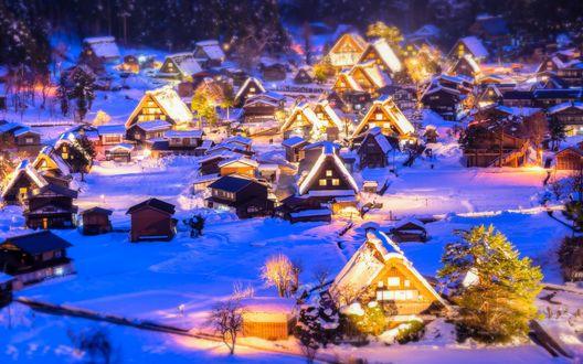 Обои Заснеженный коттеджный поселок с ярко освещенными домами в окружении деревьев, готовится к встрече новогодних и рождественских праздников