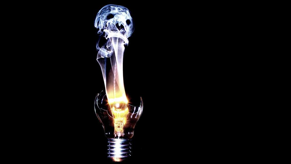 Обои для рабочего стола С расколотой электрической лампочки вырываются языки пламени и поднимается дым в виде человеческого черепа
