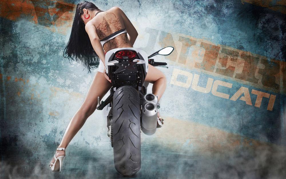 Обои для рабочего стола Девушка с тату на спине сидит на гоночном мотоцикле, на стене надпись Vinner Ducati (марка мотоцикла)