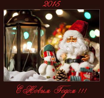 Обои Фигурки Санта-Клауса / Santa Claus и Снеговика, сидящие рядом возле декоративного фонаря с горящими в нем свечами, автор Юрий Бершадский
