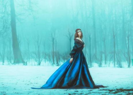Обои Стройная, темноволосая девушка с украшением на голове, в длинном, синем платье, стоящая на заснеженной опушке леса с туманом между деревьями, автор Светлана Беляева
