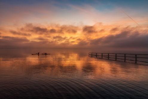 Обои Спортсмены, проводящие тренировку на байдарках, отплывающие от берега морского залива на рассвете на фоне утреннего небосклона с разноцветными облаками, автор Marzena Wieczorek