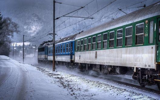 Обои Железнодорожный состав мчится мимо заснеженных гор и домов