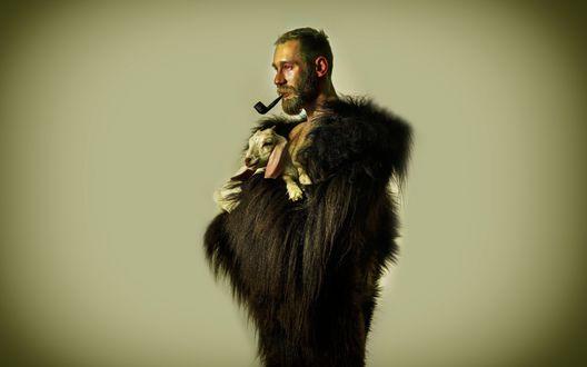 Обои Бородатый мужчина с люлькой в зубах и в меховой накидке держит на руках козленка