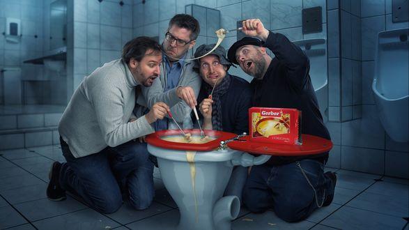Обои Мужчины сидят возле унитаза, наполненного соусом, окунают туда кусочки пищи и едят