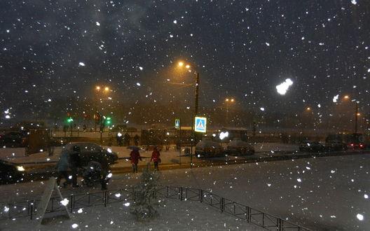 Обои Падающий снег на заснеженных улицах городской окраины на фоне ночного неба