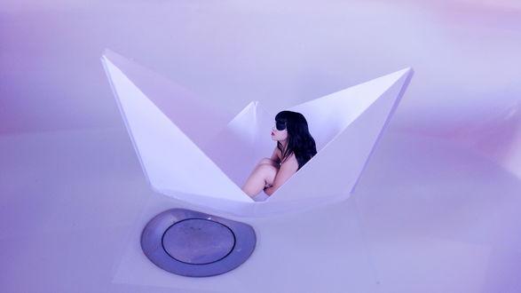 Обои Черноволосая девушка в солнцезащитных очках, сидящая в белом, бумажном кораблике, плавающем в ванне