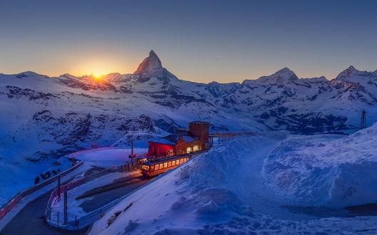 Обои Электропоезд, остановившийся у конечной станции в заснеженных горах на фоне восходящего из-за гор солнца на утреннем, безоблачном небосклоне