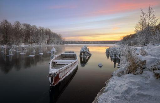 Обои Лодка, покрытая густым слоем инея, стоящая невдалеке от берега незамерзающей зимой реки на фоне заката на вечернем небосклоне, автор Денис Сорокин