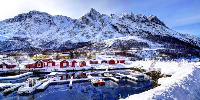 Обои Небольшой городок, стоящий в заснеженном предгорье на берегу водоема, местами покрытого тонкой кромкой льда, со стоящими на нем катерами
