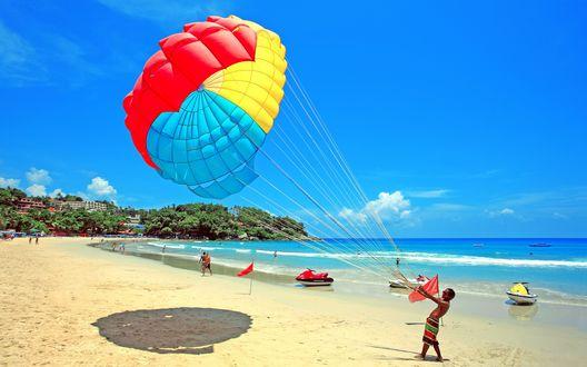 Обои Мужчина, стоящий на песчаном пляже океанского побережья, удерживает в руках на стропах купол цветного парашюта
