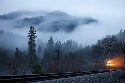 Обои Поезд с ярко горящими фарами, прицепленными товарными вагонами, проходящий через горное образование с густым, молочным туманом, окутавшим сопки, растущими деревьями по обочинам железнодорожного полотна