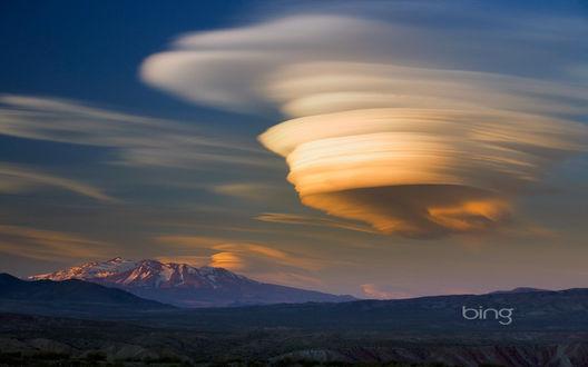 Обои Песчаное облако, образовавшееся в результате смерча на земле невдалеке от гор с заснеженными пиками вершин (bing)