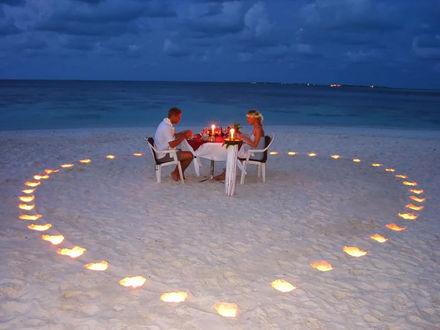Обои Романтический ужин влюбленой пары в День святого Валентина на берегу моря в окружении зажженых свечей, выложенных на песке в форме сердца