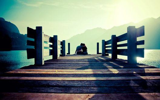 Обои На деревянном мостике, уходящем вдаль горного озера, в солнечных лучах сидит пара влюбленных