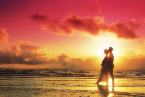 Обои Мужчина и девушка стоят обнявшись, на берегу в прибрежных волнах, на фоне заката