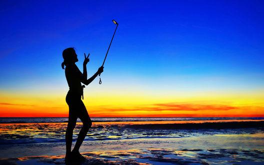 Обои Силуэт девушки, стоящей на берегу моря на фоне заката на синем небе, делающая селфи при помощи мобильного телефона