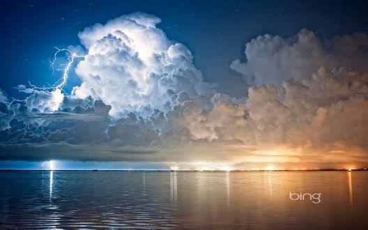 Обои Грозовое, ночное небо с белыми и серыми кучевыми облаками, сверкающими молниями над морским заливом (bing)