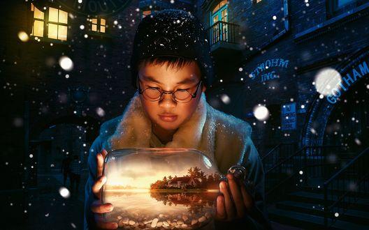 Обои Мальчик стоит под падающим снегом и держит в руках бутылку в которой виден домик стоящий у озера