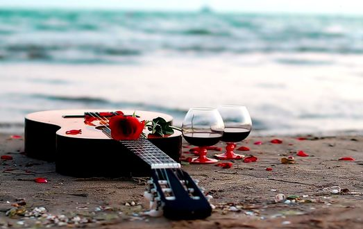 Обои На берегу моря лежит гитара, стоят два бокала вина и красная роза, шумит прибой