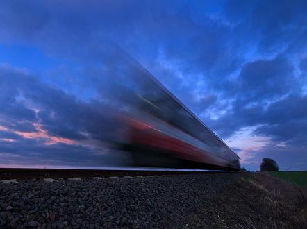 Обои Пассажирский поезд, мчавшийся на огромной скорости на фоне вечернего, пасмурного небосклона, автор Mirek Grobelski