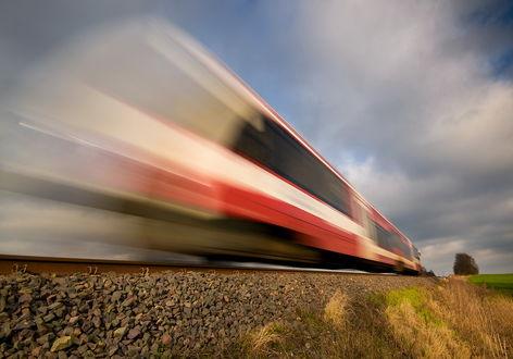 Обои Пассажирский поезд, мчавшийся на огромной скорости на фоне пасмурного небосклона с серыми, кучевыми облаками, автор Mirek Grobelski