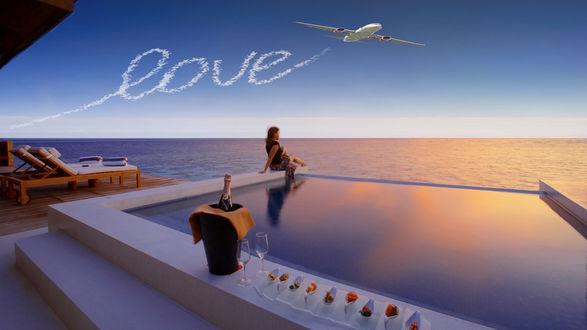 Обои Девушка сидит на краю бассейна, где стоит ведерко с шампанским, бокалы и закуски для романтического ужина, смотрит в морскую даль, в небе самолет написал слово (LOVE) любовь