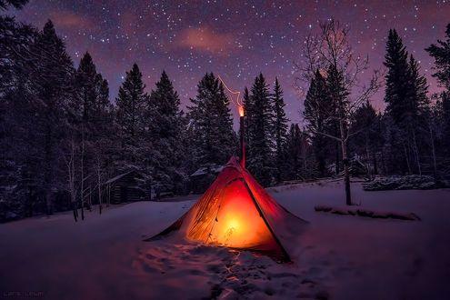 Обои В заснеженном лесу под ночным звездным небом стоит палатка, внутри освещенная светом, на верхушке палатки горит факел, автор Lars Laber