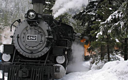 Обои Старинный паровоз с белым дымом, вьющимся из паровозных труб, проходящий через заснеженную тайгу