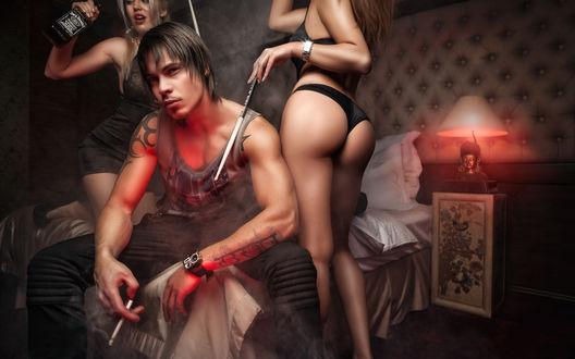 Обои Темноволосый парень с татуировками на руках, курит сидя на кровати рядом с ним танцуют две девушки в нижнем белье с бутылкой Джек Дэниэлс / Jack Daniels