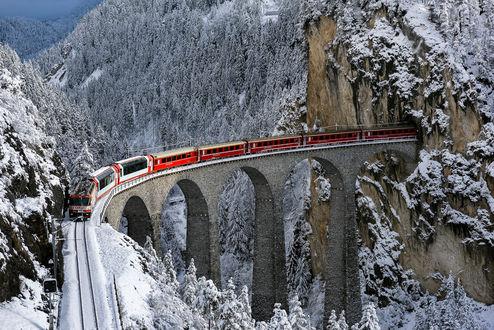 Обои Пассажирский поезд, выходящий из туннеля в горах, идущий по железнодорожному мосту, проложенному через заснеженное, горное ущелье