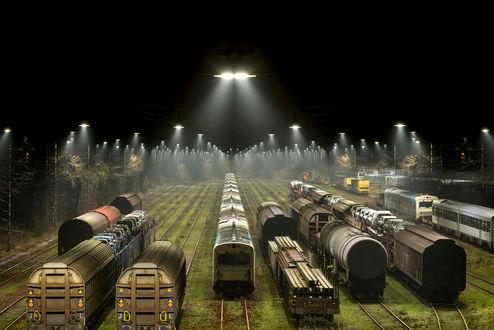 Обои Вагоны различного назначения, стоящие на запасных, железнодорожных путях, освещенные уличными фонарями на фоне ночного неба и туманной дымки