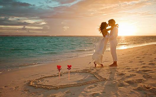 Обои На рассвете, на берегу моря влюбленные на песке нарисовали сердце, пронзили его стрелами с красными сердечками и поздравляют друг друга с Днем святого Валентина»