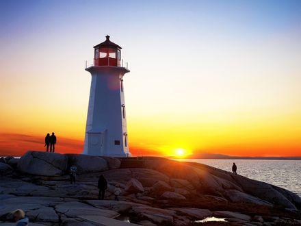 Обои Люди, стоящие возле маяка, расположенного на скалистом, морском побережье в ослепительных, солнечных лучах на утреннем, безоблачном небе