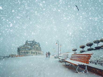 Обои Пожилая супружеская пара, идущая под хлопьями падающего снега, по морской набережной со стоящими скамейками, морским вокзалом, с парящими в воздухе морскими чайками, автор Garas Ionut