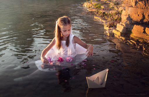 Обои Девочка в белом платье, стоящая по пояс в воде невдалеке от каменистого берега озера с лежащими у нее на подоле платья бутонами роз с плывущим рядом бумажным корабликом, автор Алексей Макаренок