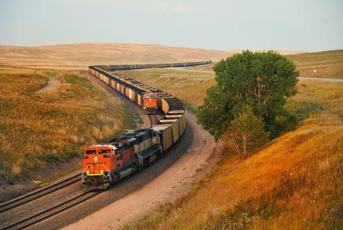 Обои Два железнодорожных состава с грузовыми платформами, двигающимися в одном направлении по холмистой местности на фоне серого небосклона